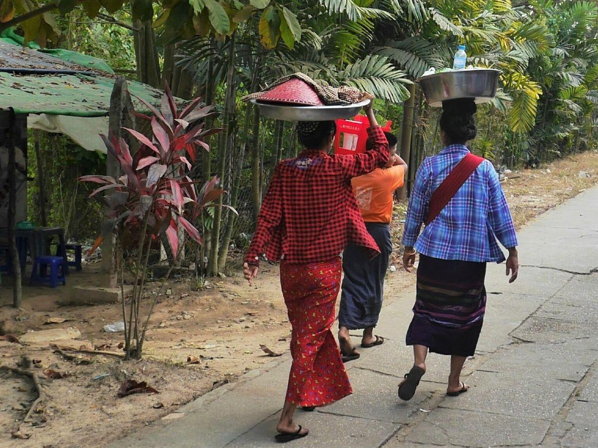 Verkäuferinnen mit Körben auf dem Kopf gehen den Bahnsteig entlang