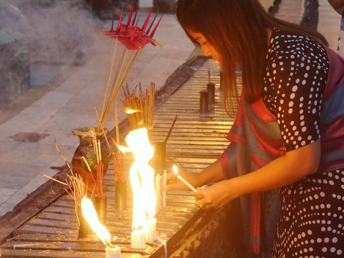 Eine Frau zündet Kerzen an