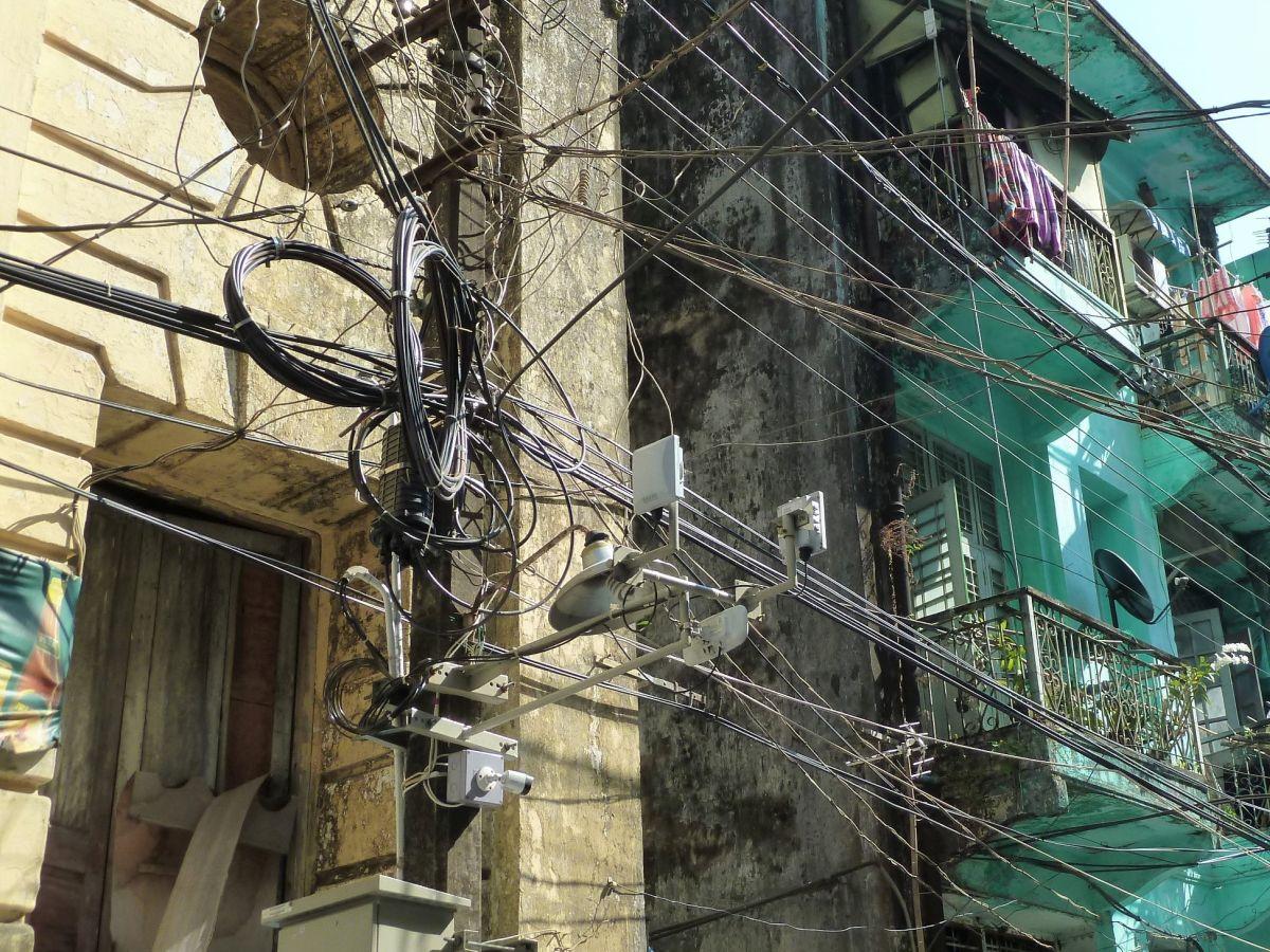Strommast mit sehr vielen verknäuelten Kabeln