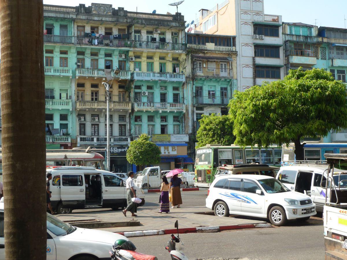 Platz mit Autos, hohen Häusern und Fußgängern