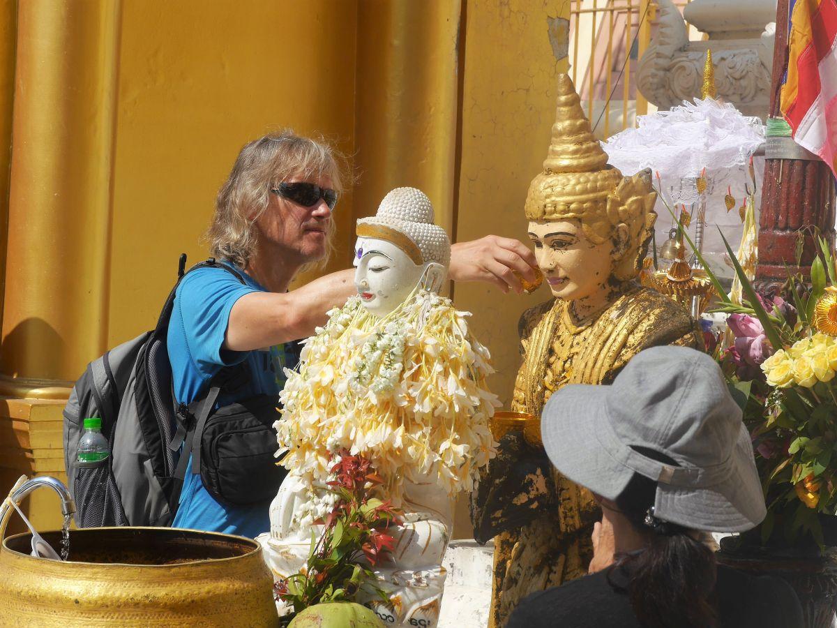 Marcus gießt Wasser über eine Buddha-Figur