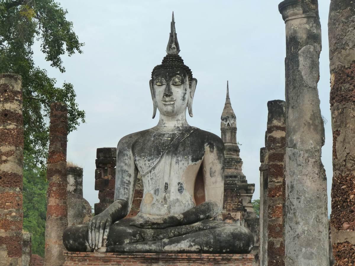 Große sitzende Buddha-Statue, umgeben von Säulen.