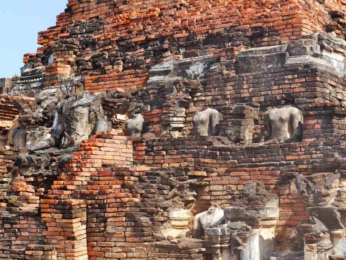 Viele zerborstene Buddha-Statuen entlang des Tempels.