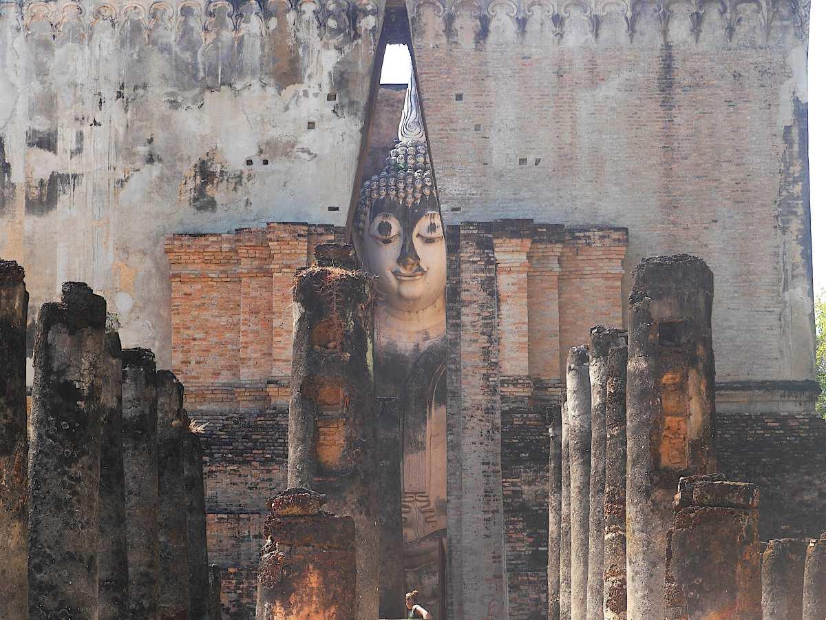 Tempel mit riesiger Buddhastatue, die durch Gebäudespalt zu sehen ist.