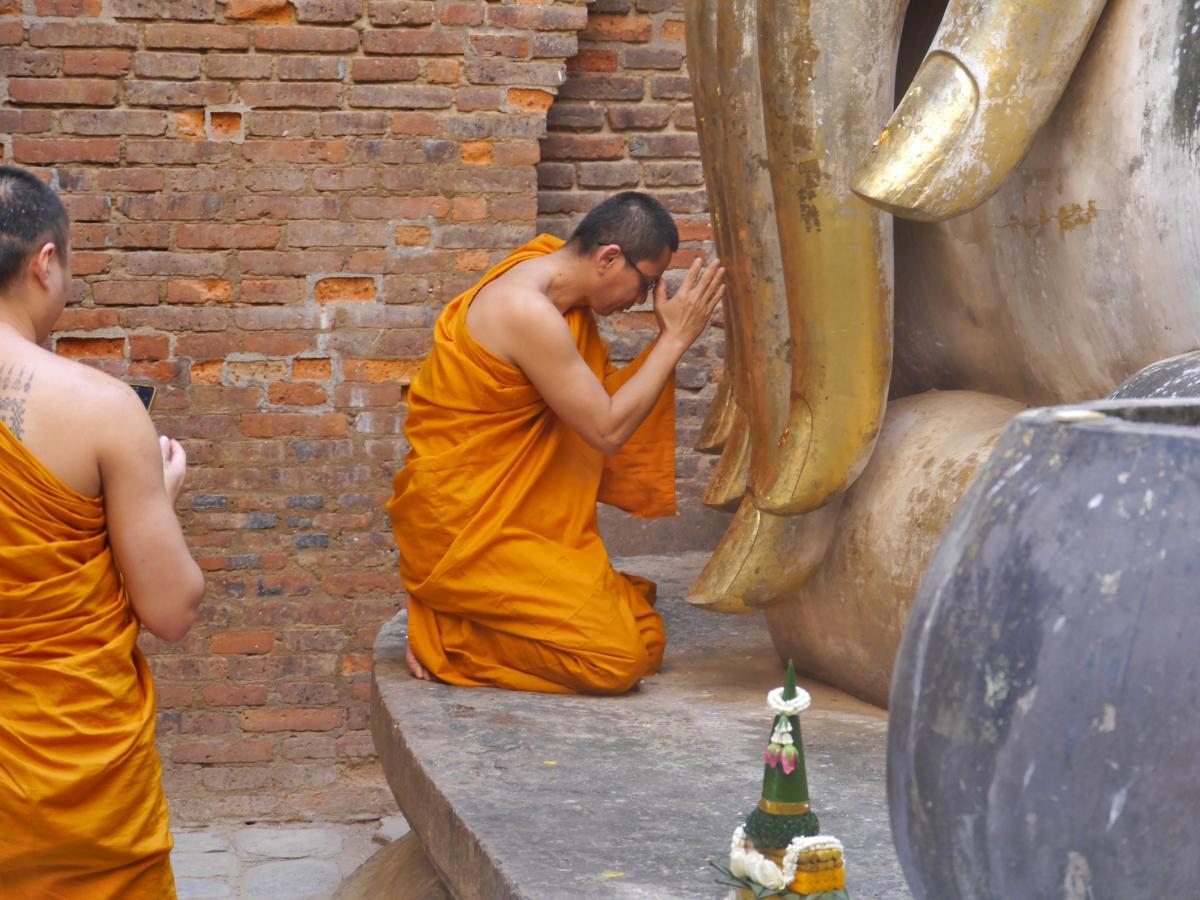 Mönch in Gebetshaltung wird von zweitem Mönch fotografiert.