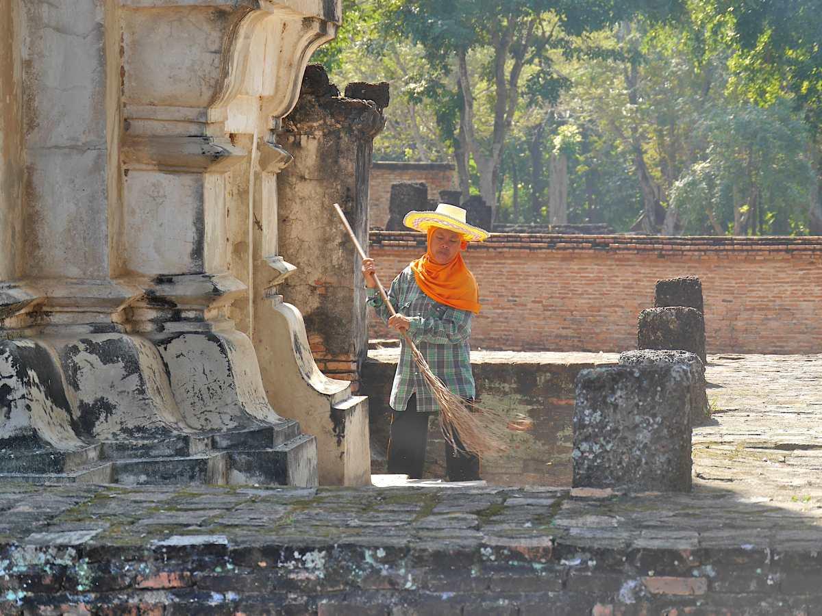 Person mit Sonnenhut und Reisigbesen vor dem Tempel.