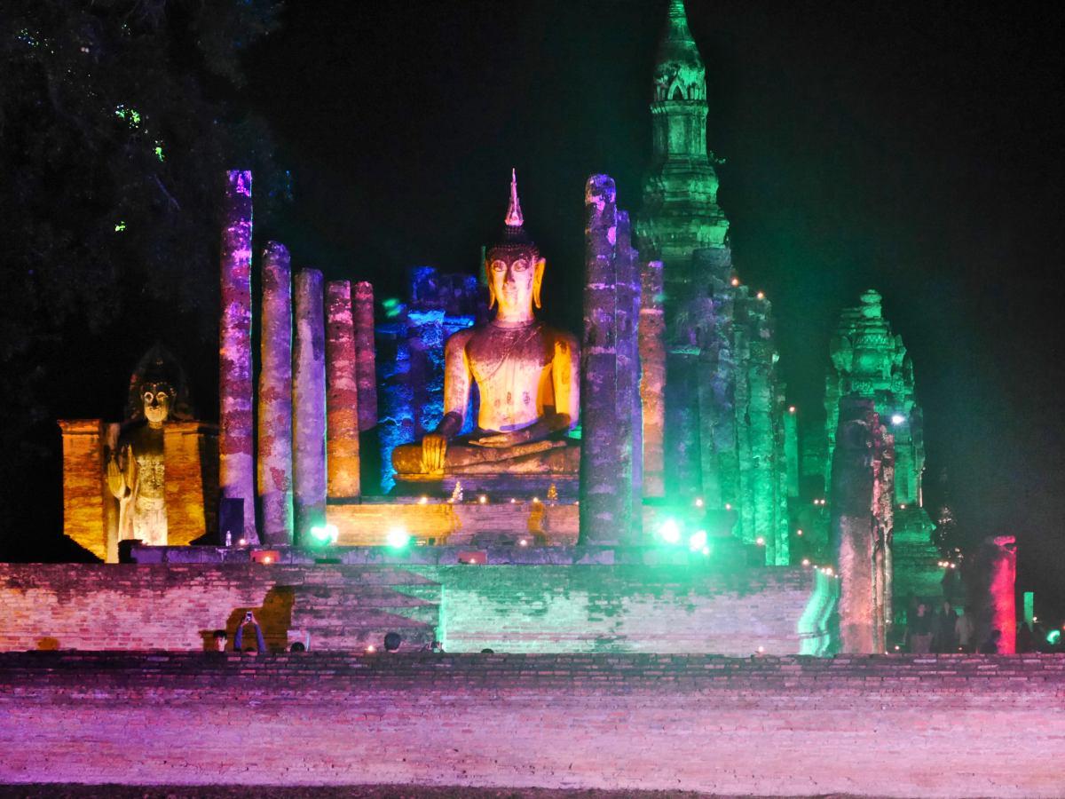 Buddha und Chedis in bunten Farben angestrahlt.