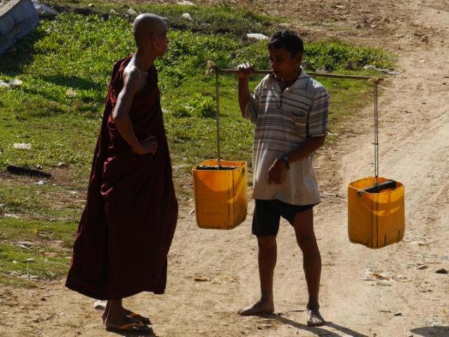 Ein Mann trägt ein Joch mit zwei Eimern und unterhält sich mit einem buddhistischen Mönch in roter Kleidung
