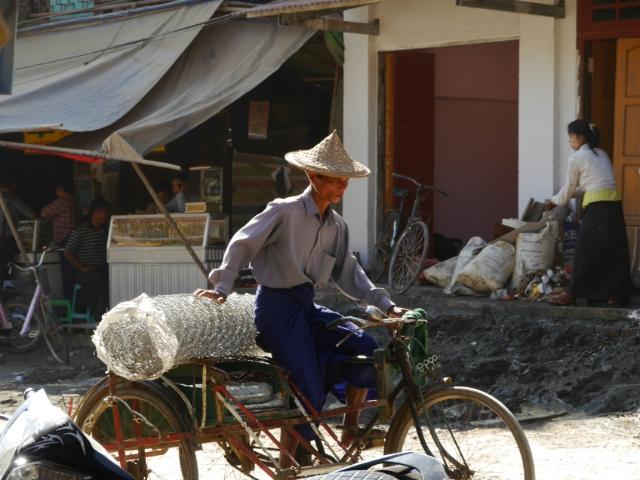 Ein Mann transportiert eine große Drahtzaunrolle auf dem Fahrrad