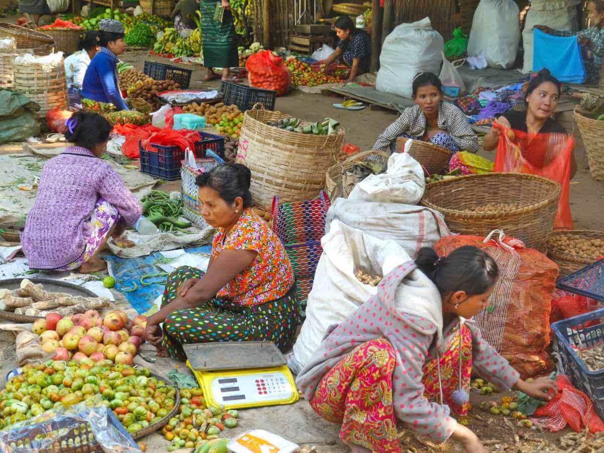Marktfrauen sitzen auf dem Boden vor ihrer Ware.