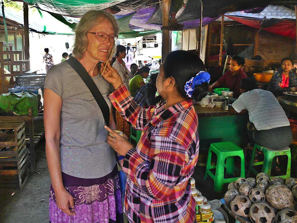 Frau trägt Thanaka auf Ginas Wangen auf.
