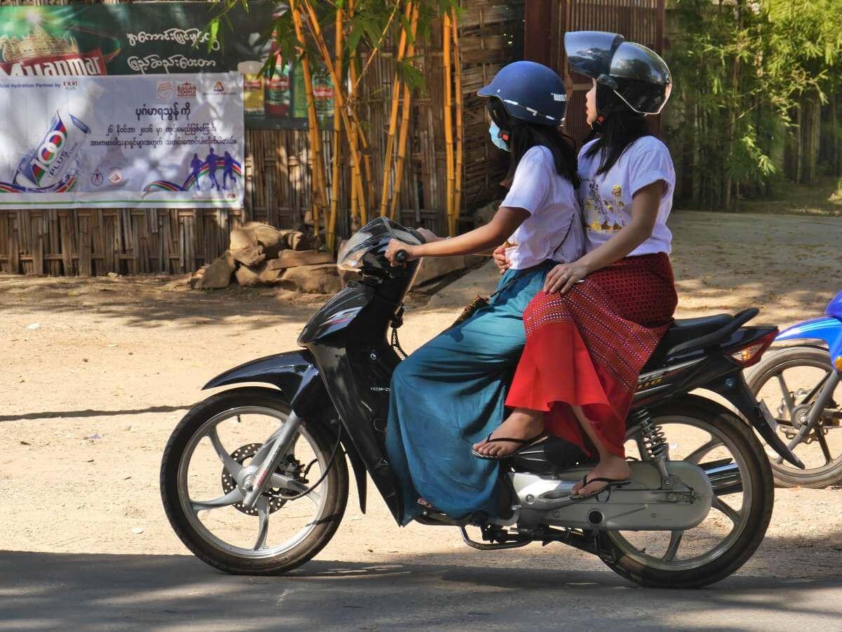 Zwei junge Frauen auf dem Motorroller, die hintere im Damensitz.