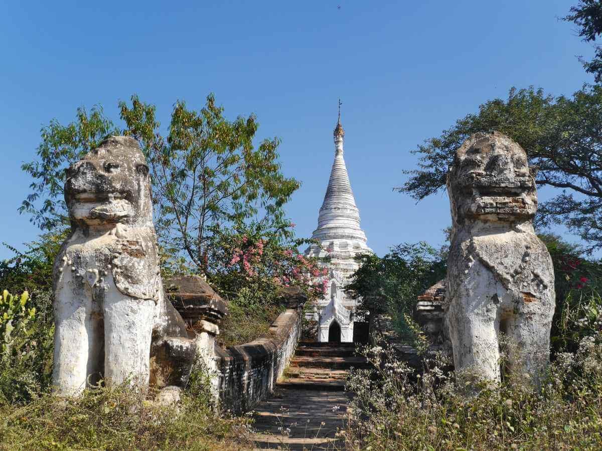 Weißer Stupa mit flankierenden Steinlöwen.