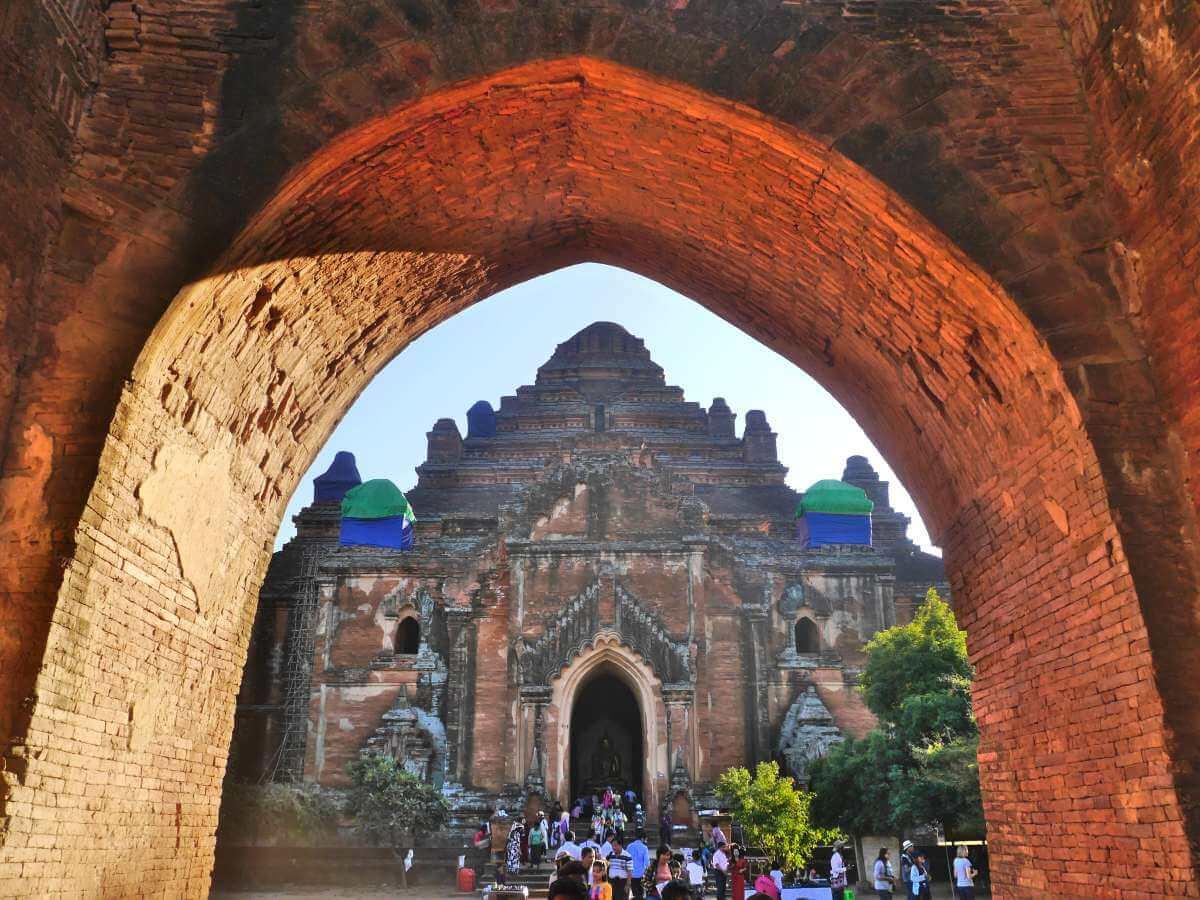 Blick durch Torbogen auf Tempeleingang mit vielen Touristen.