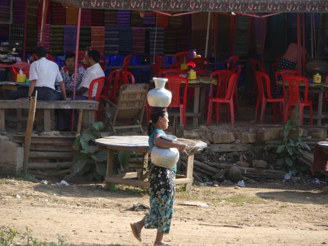 Eine Frau trägt je ein Wassergefäß auf dem Kopf und auf der Hüfte