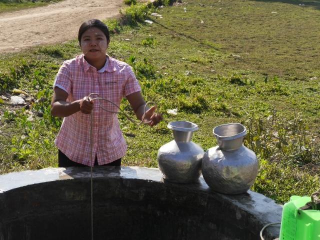 Frau mit zwei Schöpfgefäßen steht am Brunnen