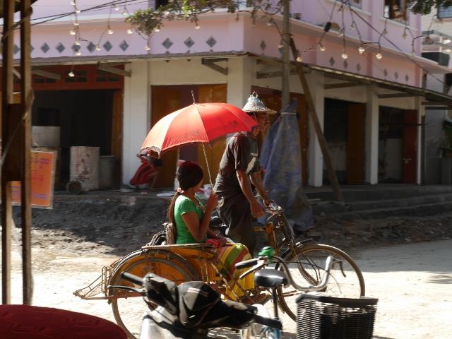 Dreirädriges Fahrrad, Mann fährt, Frau mit Sonnenschirm auf dem Beifahrersitz