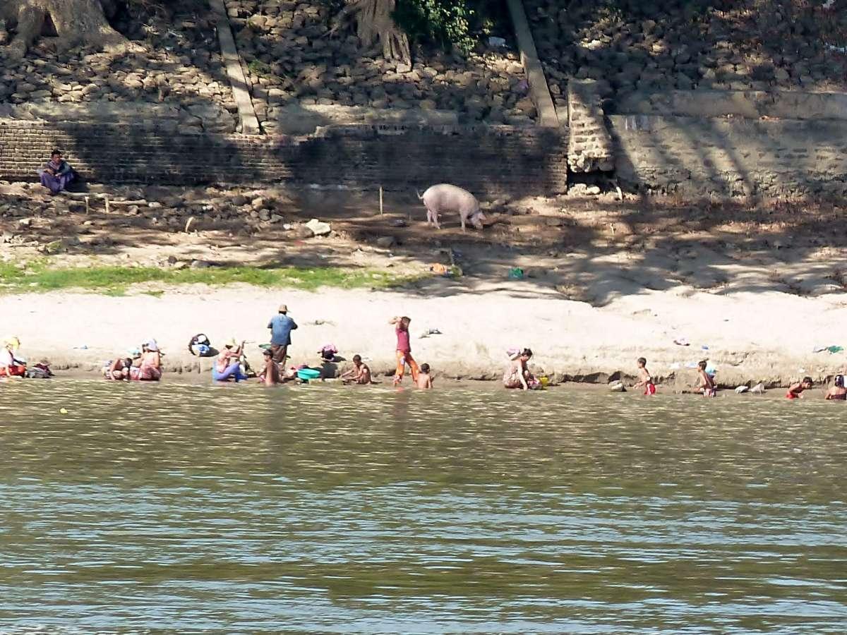 Menschen baden und waschen Wäsche am Ufer