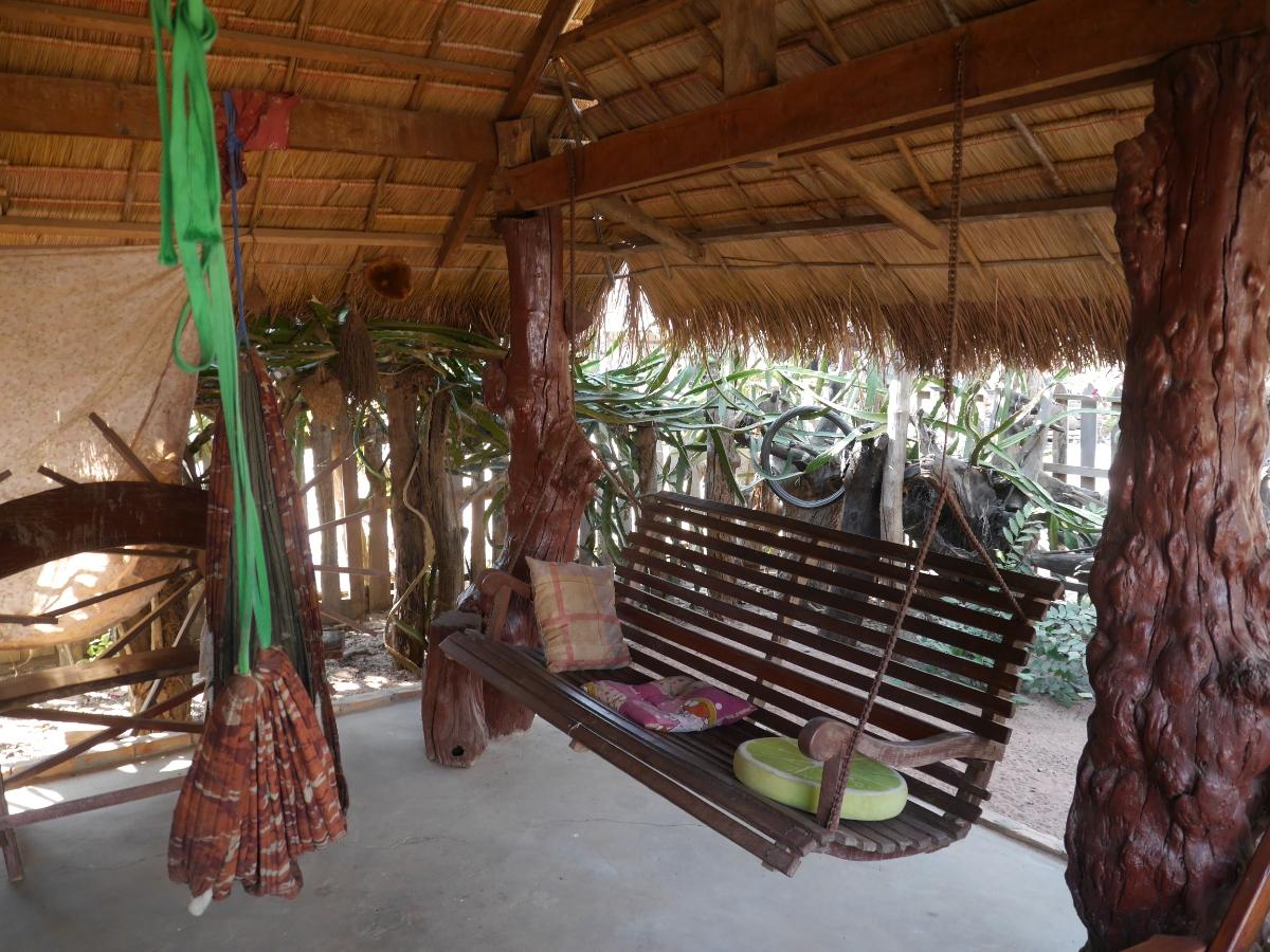 Bank und Hängematten unter Palmblätterdach