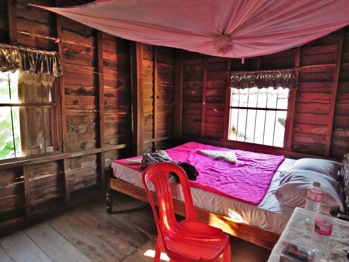 Zimmer mit bunter Bettdecke und Moskitonetz.