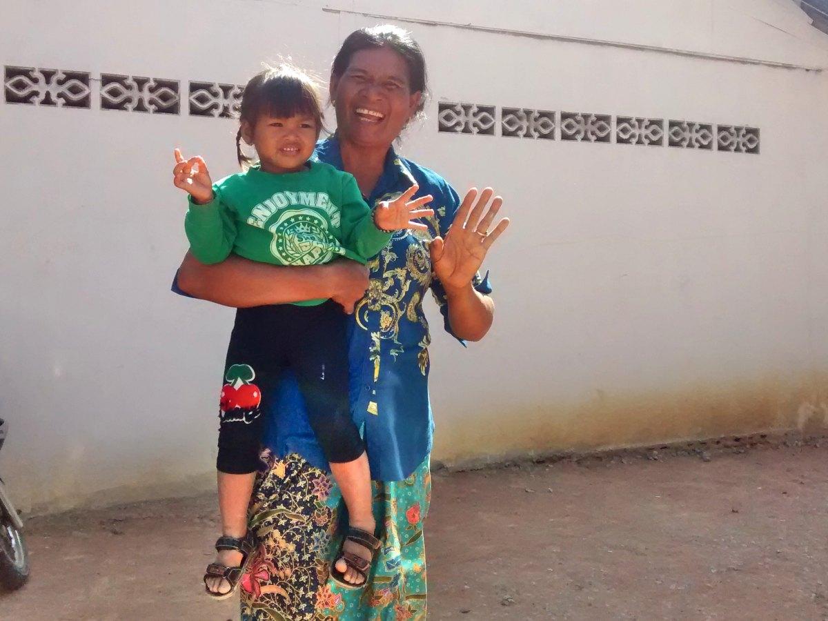 Frau mit Kind auf dem Arm winkt freundlich.
