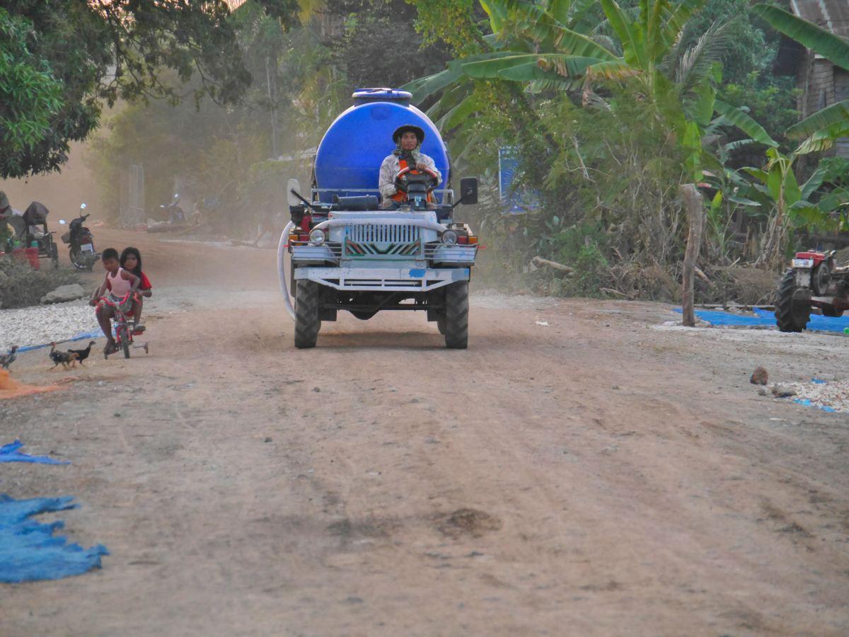 Fahrzeug auf staubiger Dorfstraße in Banteay Chhmar.