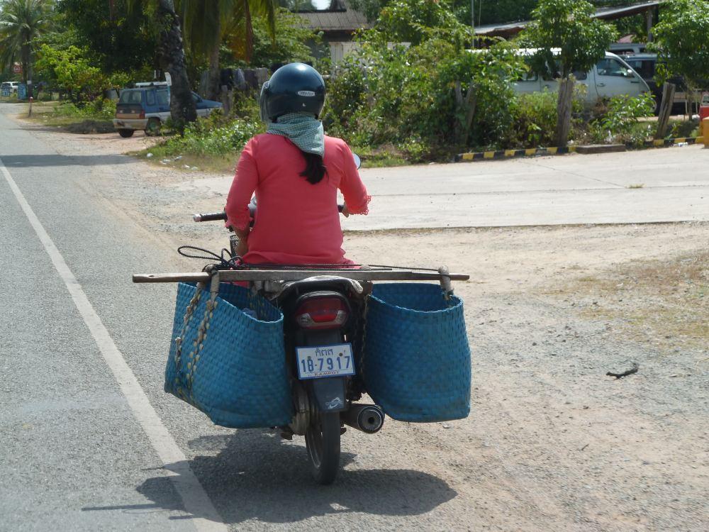 Frau auf Motorroller mit großem Gepäck.
