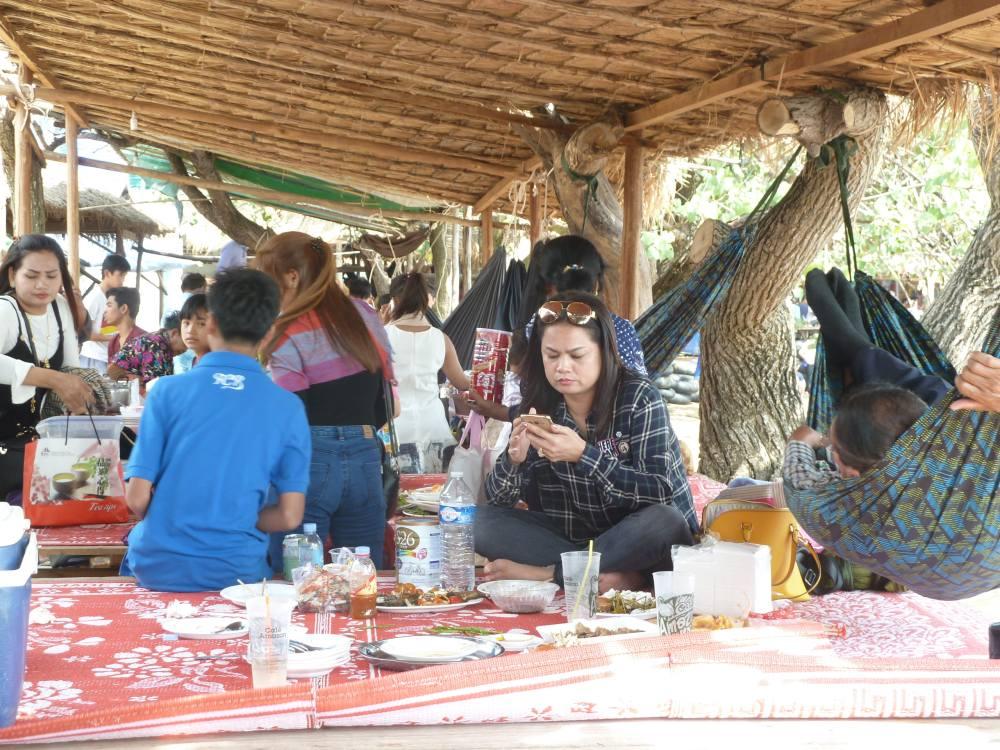 Menschen sitzen auf dem Boden und essen.