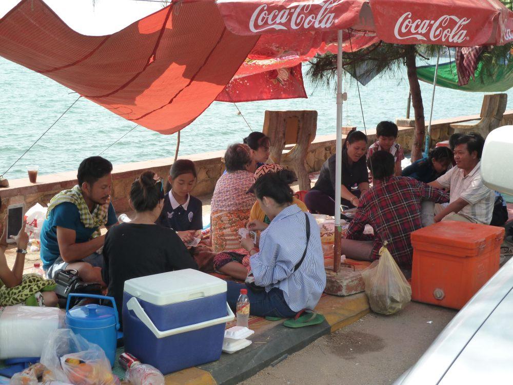 Familien sitzen auf der Promenade beim Picknick.