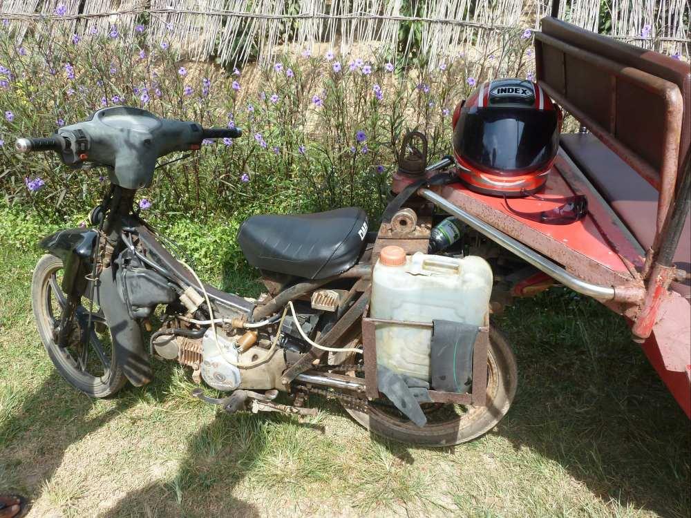 Kleines Motorrad mit Wasserkanister an der Seite.