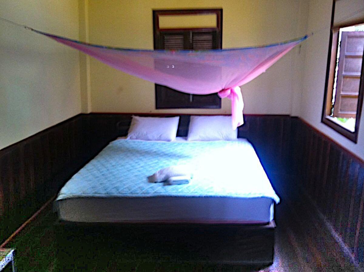 Zimmer mit Doppelbett und pinkfarbenem Moskitonetz