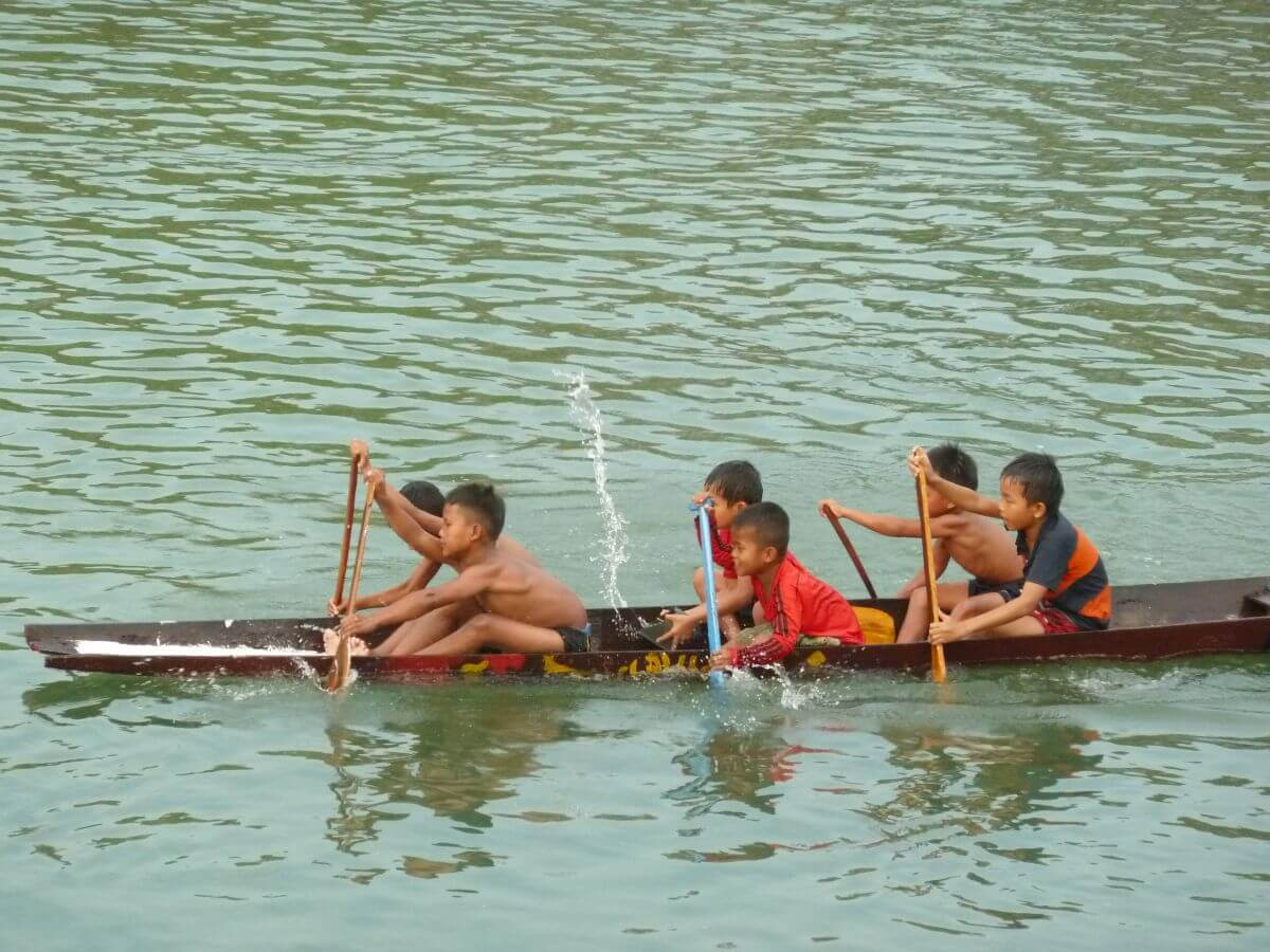 Sechs Jungen in einem schmalen Boot