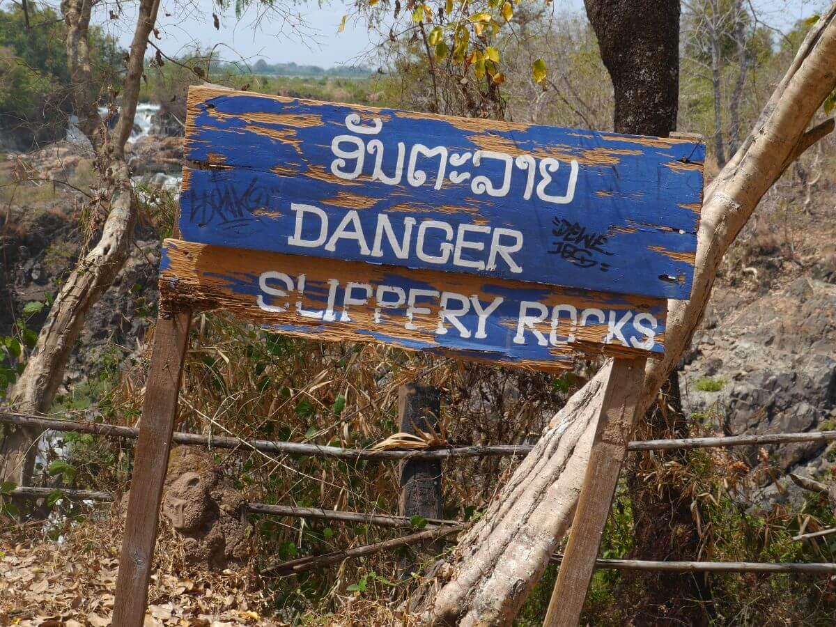 Marodes Holzschild, dass vor rutschigen Felsen warnt