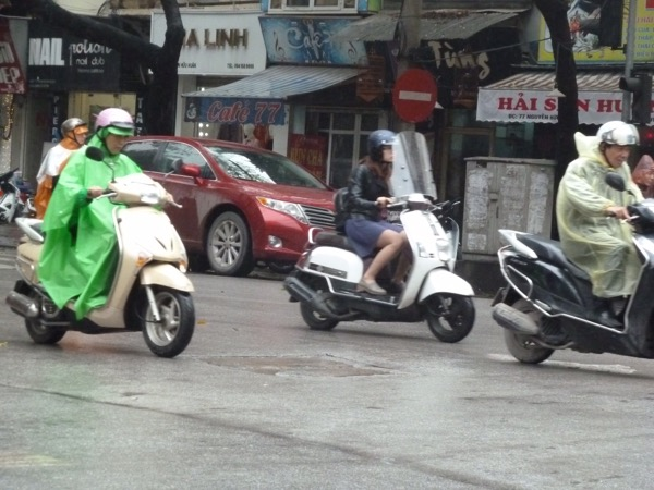 Rollerfahrer bei Regen in Hanoi.