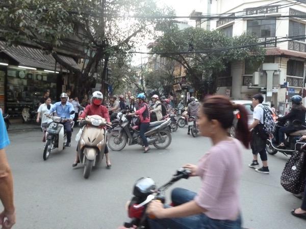 Gewusel von Rollerfahrern auf einer Kreuzung in Hanoi.