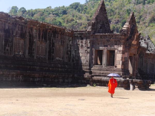 Mönch in leuchtendem Orange mit Sonnenschirm.