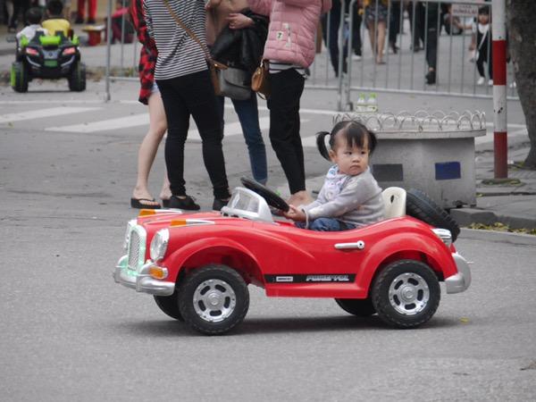 Kleines Mädchen in elektrischem Spielzeugauto.