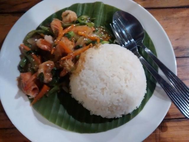 Reis und Curry auf Bananenblatt angerichtet.