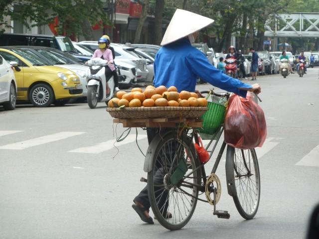 Straßenhändlerin mit Fahrrad und Früchtekorb.