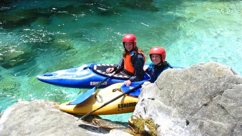 Zwei Kajak-Paddler auf dem türkisen Wasser der Soca.