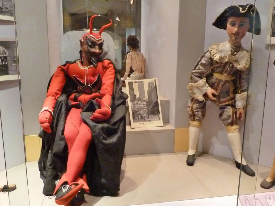 Marionette als Teufel sitzt im Sessel