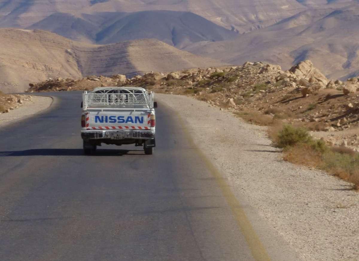 Pickup fährt auf der Straße durch die Wüste