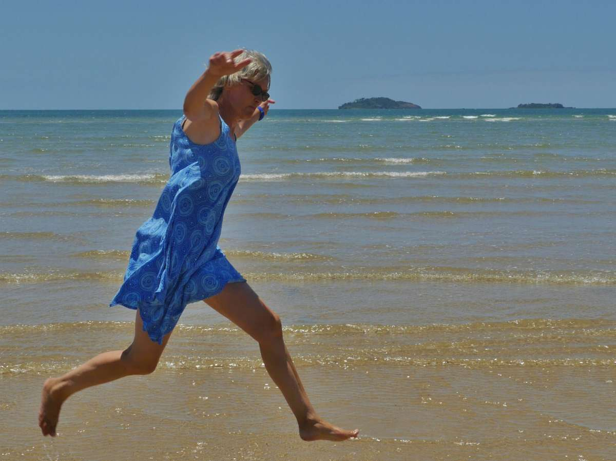 Frau im Sommerkleid am Strand