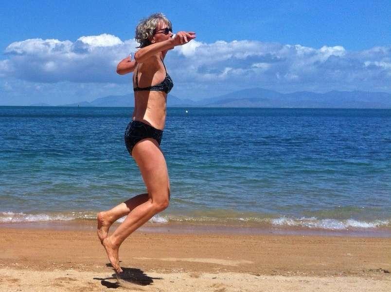 Frau springt am Strand unbeholfen