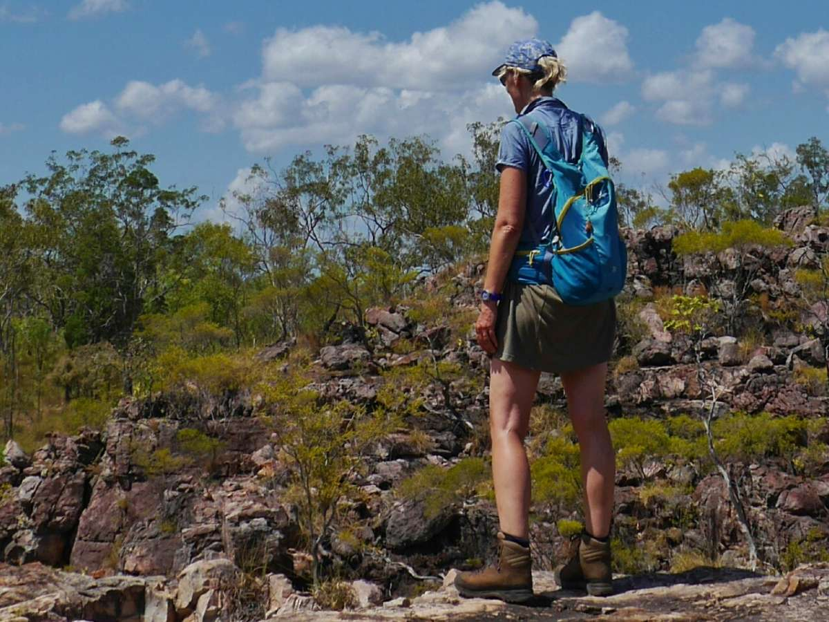 Frau in Wanderkleidung steht am Felshang