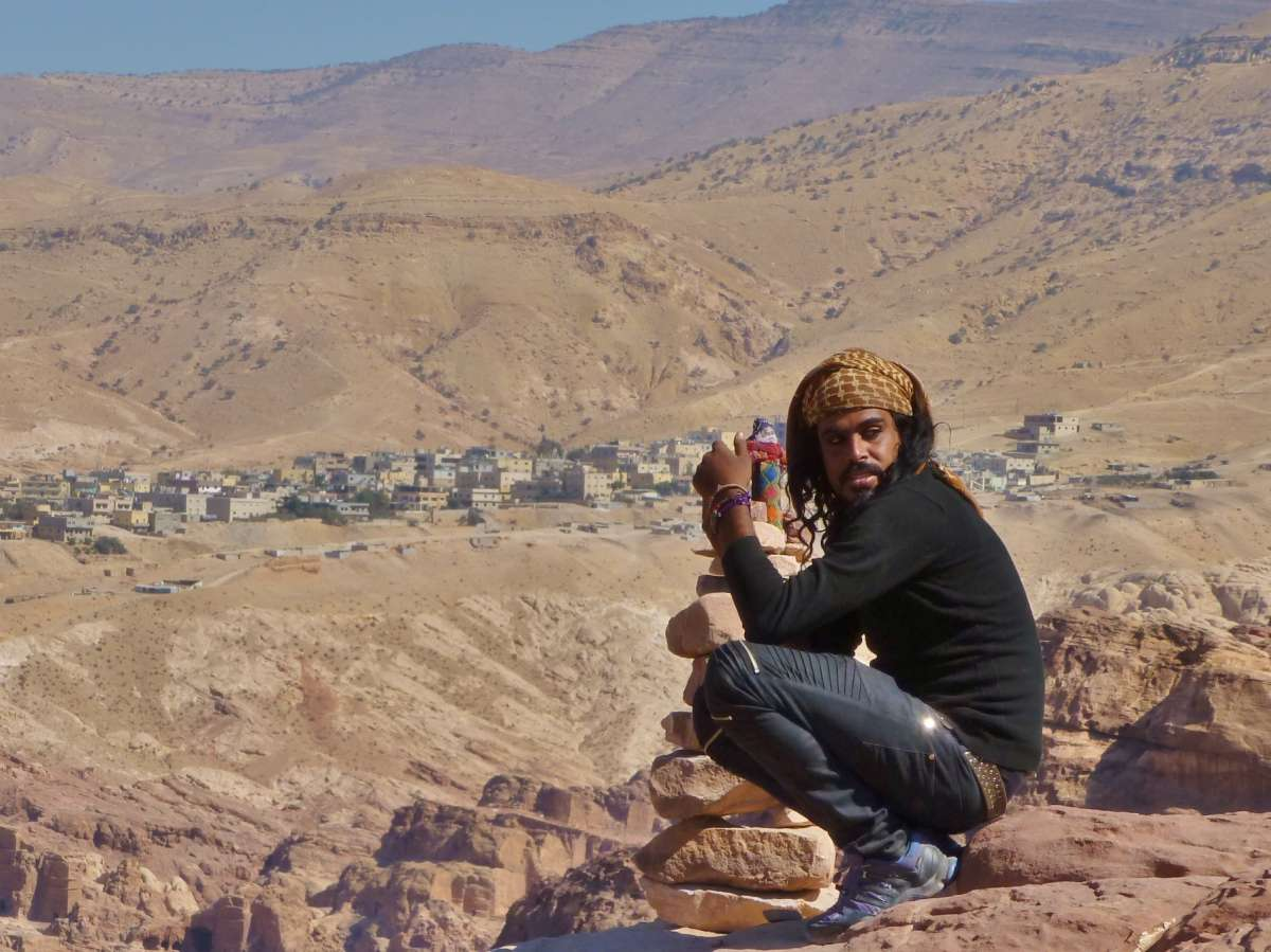 Beduine hockt auf Felsvorsprung in Petra