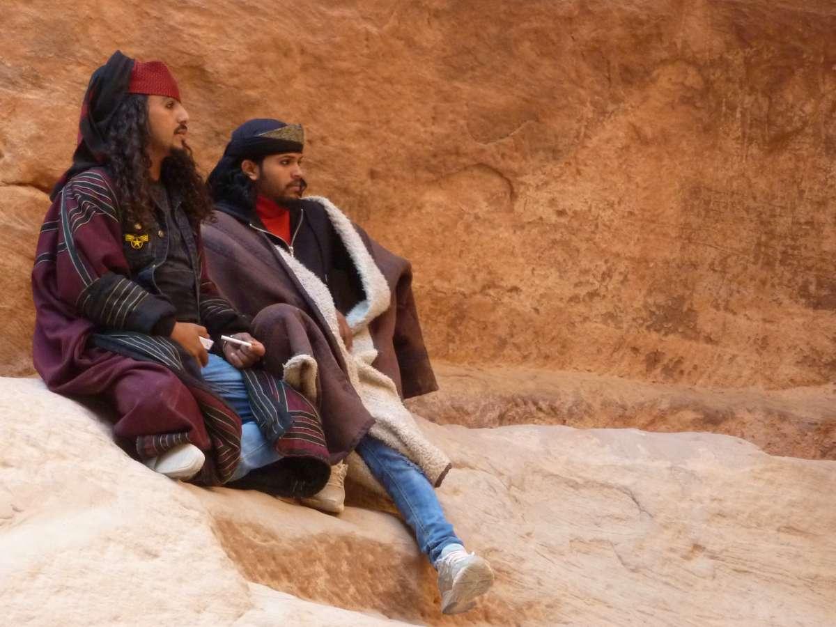 zwei Beduinen mit langen Locken und Kopftüchern sitzen an der Felswand