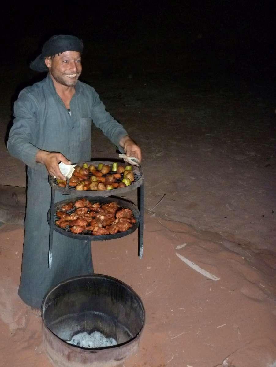 Beduine holt Gestell mit Essen aus dem Erdofen