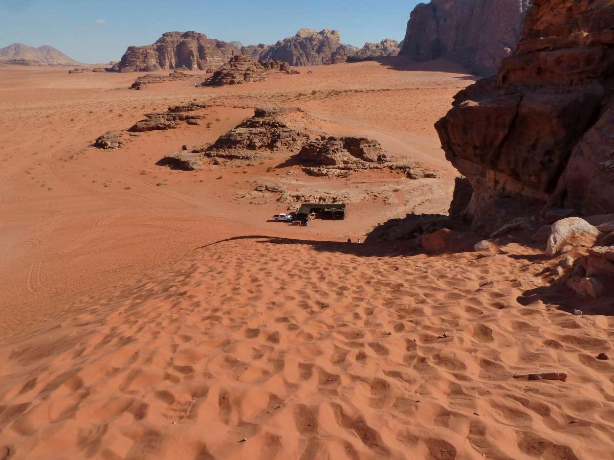 Blick die Düne hinunter, unten steht winzig klein der Jeep