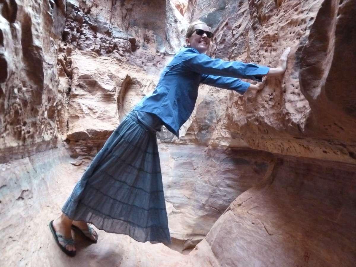 Victoria stützt sich mit Händen und Füßen an den Seiten des Canyons ab